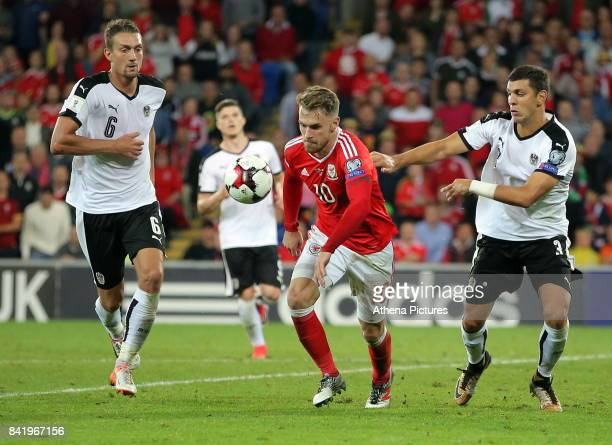 Aaron Ramsey of Wales prepares to take a shot while closely marked by Stefan Ilsanker and Aleksandar Dragovic of Austria during the FIFA World Cup...