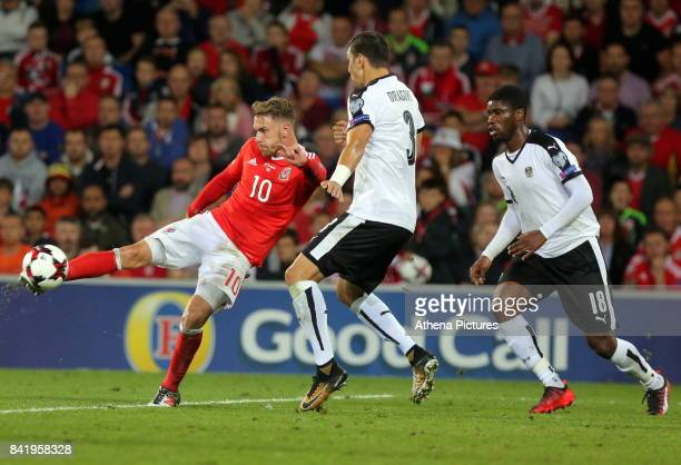 Aaron Ramsey of Wales takes a shot while closely marked by Aleksandar Dragovic of Austria and team mate Kevin Danso during the FIFA World Cup...