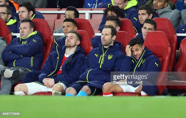 Aaron Ramsey Petr Cech and Alexis Sanchez of Arsenal watch from the bench during the UEFA Champions League Round of 16 second leg match between...