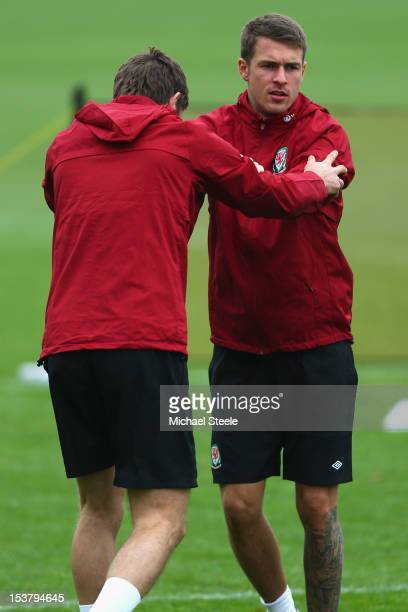 Aaron Ramsey stretches alongside Sam Ricketts during the Wales training session at the Vale Resort on October 9 2012 in Cardiff Wales
