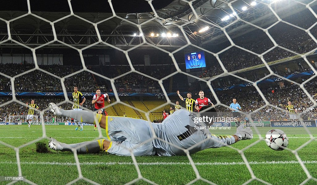 Aaron Ramsey's shot is fumbled by Fenerbahce goalkeeper Volkan Demirel for the 2nd Arsenal goal the UEFA Champions League Play Off first leg match between Fenerbache SK and Arsenal FC at Sukru Saracoglu Stadium on August 21, 2013 in Istanbul, Turkey.