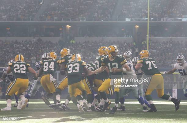 Aaron Rodgers hands the ball to Aaron Jones of the Green Bay Packers at ATT Stadium on October 8 2017 in Arlington Texas