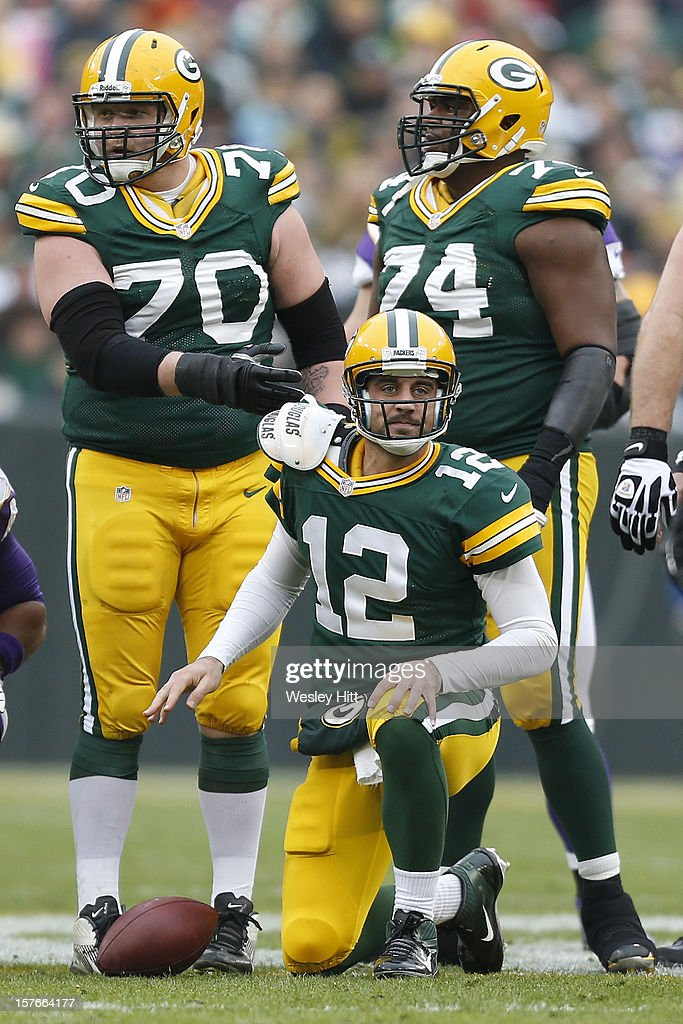 Aaron Rodgers #12 is helped up by T.J. Lang #70 of the Green Bay Packers after being sacked during a game against the Minnesota Vikings at Lambeau Field on December 2, 2012 in Green Bay, Wisconsin. The Packers defeated the Vikings 23-14.