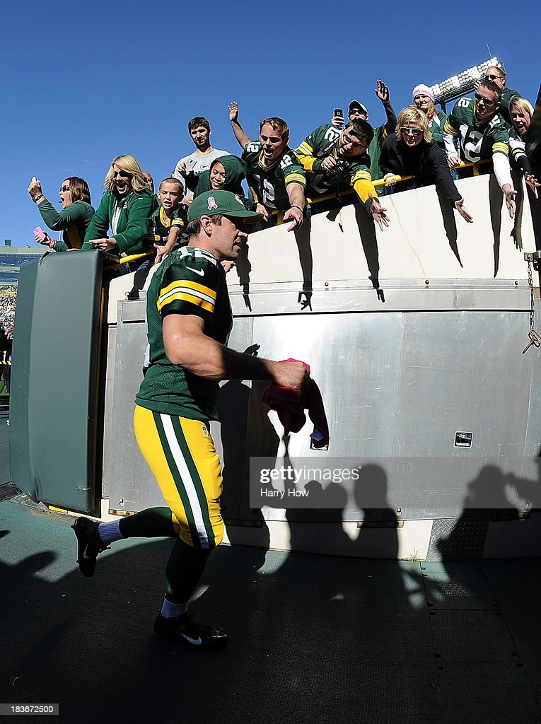 Aaron Rodgers #12 of the Green Bay Packers celebrates a 22-9 win over the Detroit Lions with fans as he leaves the field at Lambeau Field on October 6, 2013 in Green Bay, Wisconsin.