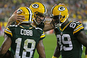 Aaron Rodgers of the Green Bay Packers congratulates Randall Cobb and James Jones after a touchdown against the Kansas City Chiefs at Lambeau Field...