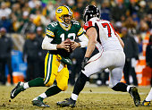 Aaron Rodgers of the Green Bay Packers escapes the tackle of Kroy Biermann of the Atlanta Falcons in the third quarter at Lambeau Field on December 8...