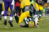 Aaron Rodgers of the Green Bay Packers falls after throwing a pass during the second quarter against the Minnesota Vikings at Lambeau Field on...