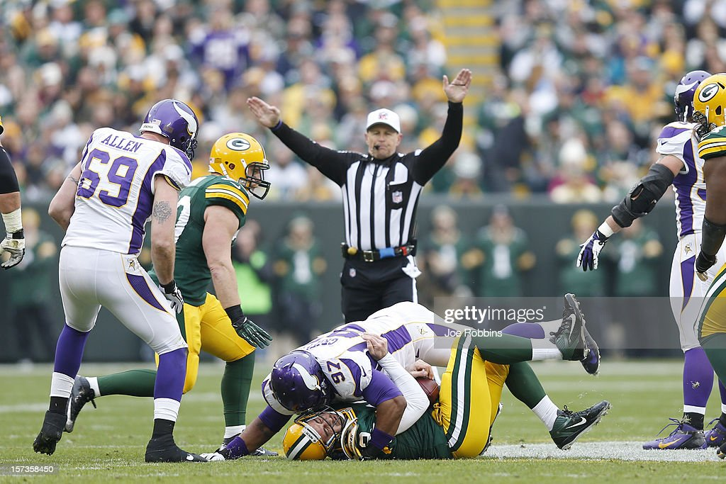 Aaron Rodgers #12 of the Green Bay Packers gets tackled by Everson Griffen #97 of the Minnesota Vikings during the game at Lambeau Field on December 2, 2012 in Green Bay, Wisconsin. The Packers won 23-14.