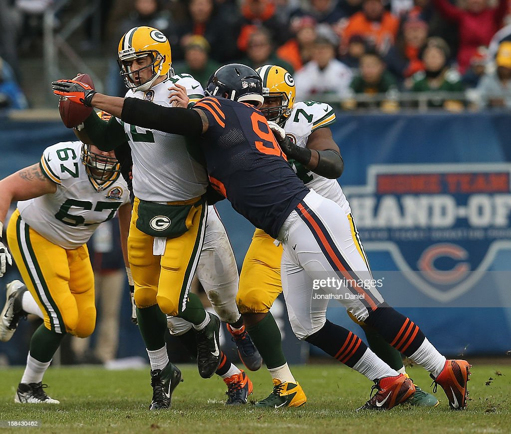 Aaron Rodgers #12 of the Green Bay Packers is sacked by Julius Peppers #90 of the Chicago Bears at Soldier Field on December 16, 2012 in Chicago, Illinois.