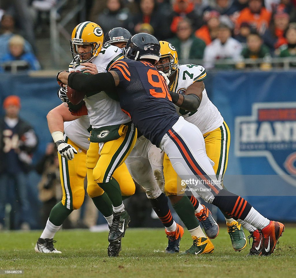 Aaron Rodgers #12 of the Green Bay Packers is sacked by Julius Peppers #90 of the Chicago Bears at Soldier Field on December 16, 2012 in Chicago, Illinois. The Packers defeated the Bears 21-13.