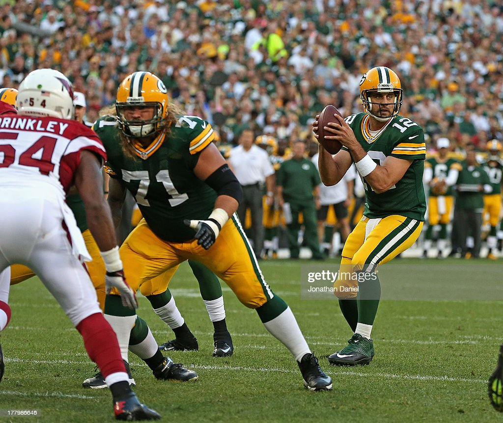 Aaron Rodgers #12 of the Green Bay Packers looks for a receiver as Josh Sitton #71 prepares to block Jasper Brinkley #54 of the Arizona Cardinals at Lambeau Field on August 9, 2013 in Green Bay, Wisconsin. The Cardinals defeated the Packers 17-0.