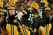 Aaron Rodgers of the Green Bay Packers looks on in the fourth quarter against the New York Giants during their NFC Divisional playoff game at Lambeau...