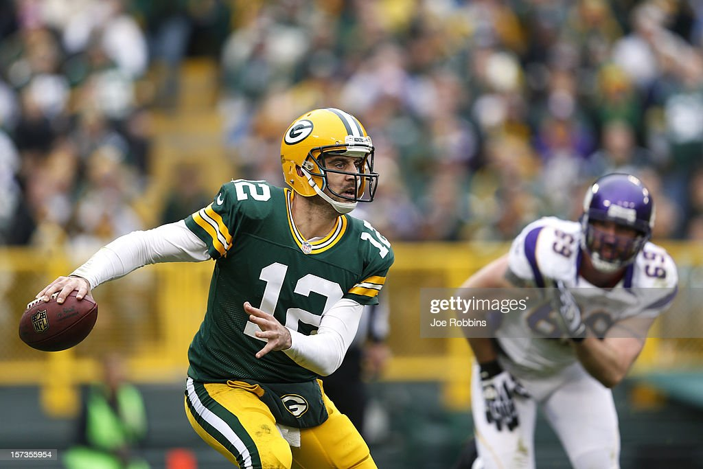 Aaron Rodgers #12 of the Green Bay Packers looks to pass the ball while under pressure from Jared Allen #69 of the Minnesota Vikings during the first half of the game at Lambeau Field on December 2, 2012 in Green Bay, Wisconsin.
