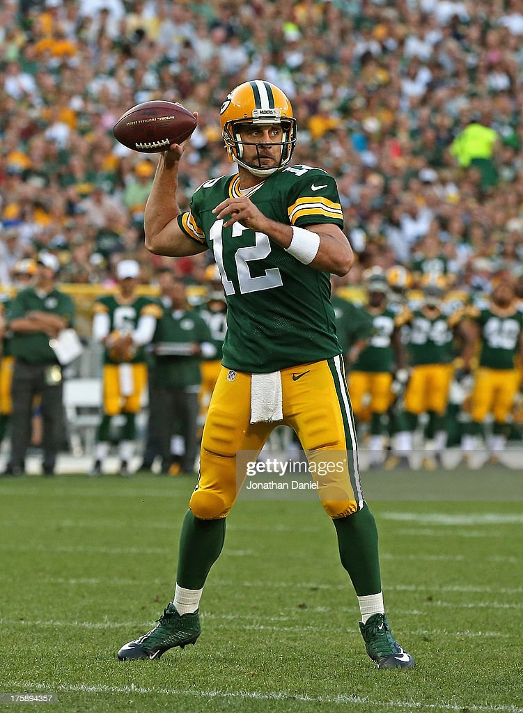 Aaron Rodgers #12 of the Green Bay Packers passes against the Arizona Cardinals at Lambeau Field on August 9, 2013 in Green Bay, Wisconsin.