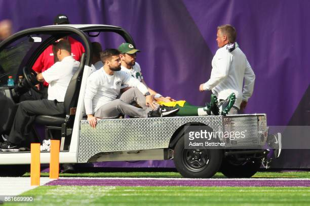 Aaron Rodgers of the Green Bay Packers rides a cart into the locker room after being injured during the first quarter of the game against the...