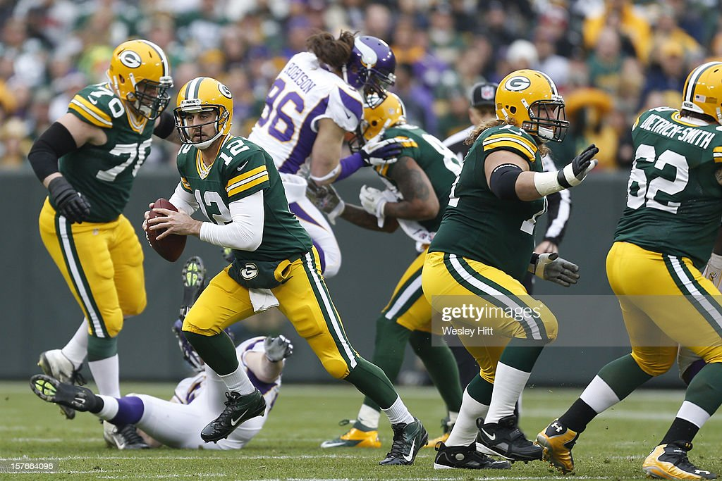 Aaron Rodgers #12 of the Green Bay Packers rolls out of the pocket during a game against the Minnesota Vikings at Lambeau Field on December 2, 2012 in Green Bay, Wisconsin. The Packers defeated the Vikings 23-14.