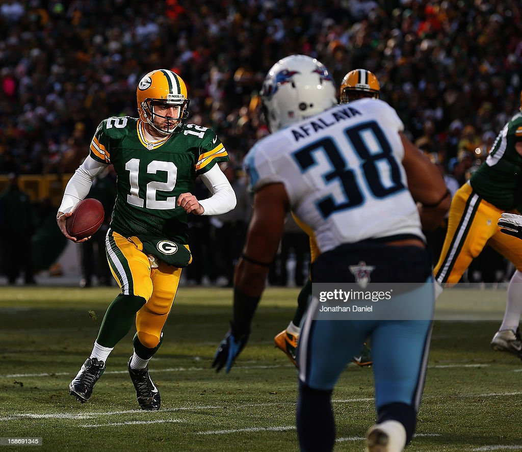 <a gi-track='captionPersonalityLinkClicked' href=/galleries/search?phrase=Aaron+Rodgers+-+American+Football+Quarterback&family=editorial&specificpeople=215257 ng-click='$event.stopPropagation()'>Aaron Rodgers</a> #12 of the Green Bay Packers runs for a touchdown against Al Afalava #38 of the Tennessee Titans at Lambeau Field on December 23, 2012 in Green Bay, Wisconsin. The Packers defeated the Titans 55-7.