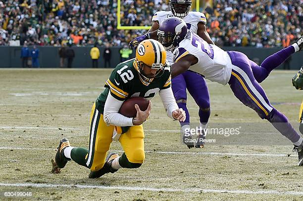 Aaron Rodgers of the Green Bay Packers rushes for a touchdown during the second quarter of a game of a game against the Minnesota Vikings at Lambeau...