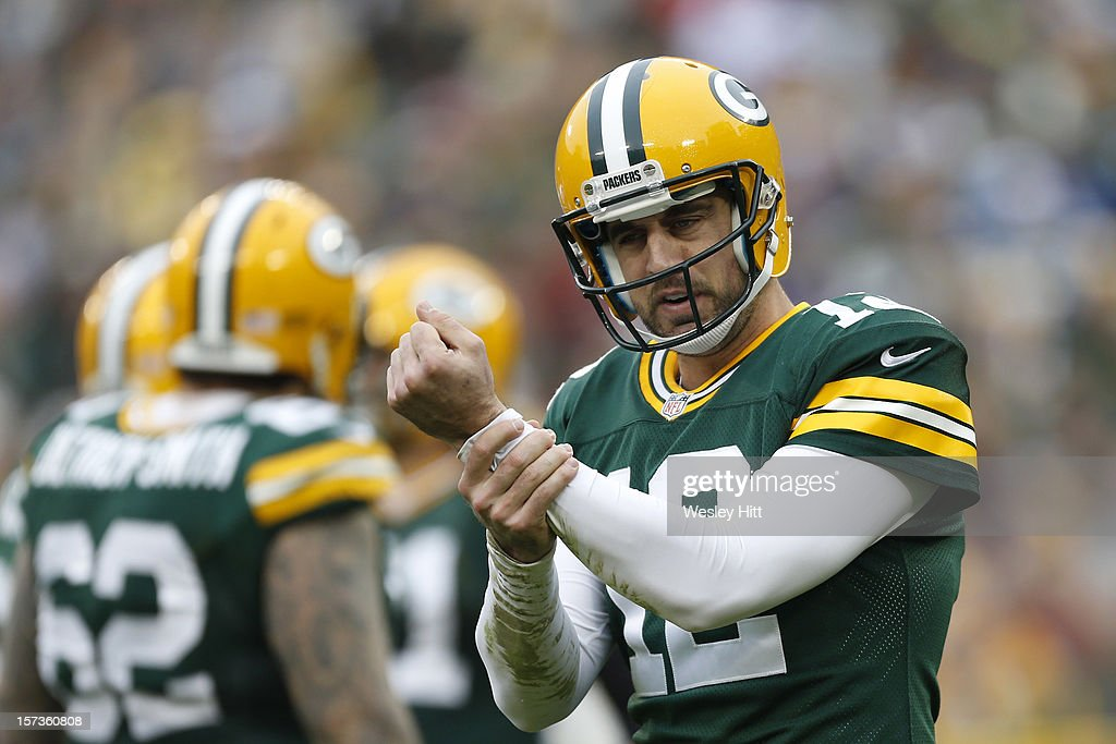 Aaron Rodgers #12 of the Green Bay Packers signals to the official for a hold during a game against the Minnesota Vikings at Lambeau Field on December 2, 2012 in Green Bay, Wisconsin. The Packers defeated the Vikings 23-14.