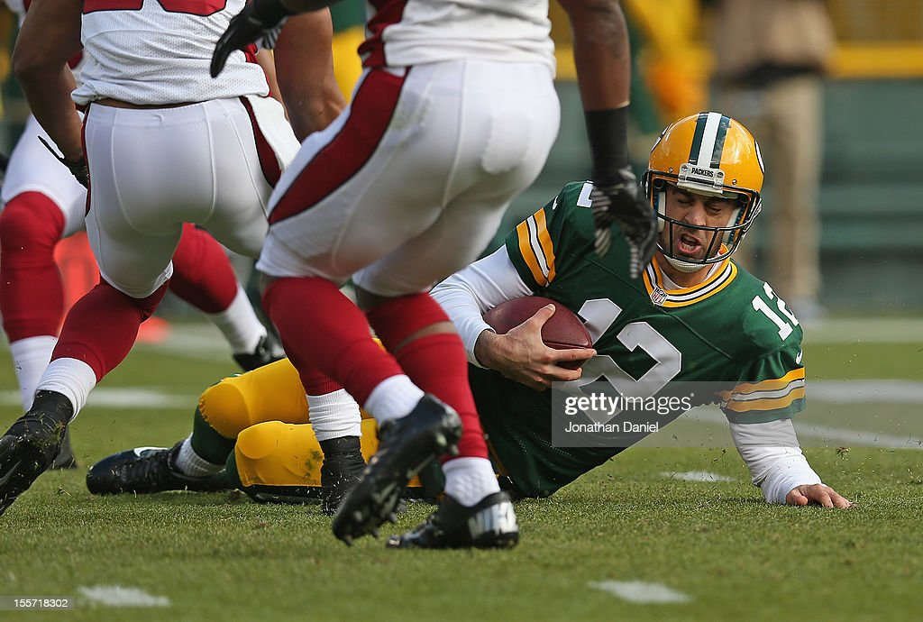 <a gi-track='captionPersonalityLinkClicked' href=/galleries/search?phrase=Aaron+Rodgers+-+American+Football+Quarterback&family=editorial&specificpeople=215257 ng-click='$event.stopPropagation()'>Aaron Rodgers</a> #12 of the Green Bay Packers slides to a stop after a run against the Arizona Cardinals at Lambeau Field on November 4, 2012 in Green Bay, Wisconsin. The Packers defeated the Cardinals 31-17.