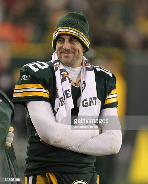 Aaron Rodgers of the Green Bay Packers smiles at a teammate on the sidelines in the 4th quarter against the Minnesota Vikings at Lambeau Field on...