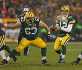 Aaron Rodgers of the Green Bay Packers takes the snap from Jeff Saturday against the Detroit Lions at Lambeau Field on December 9 2012 in Green Bay...