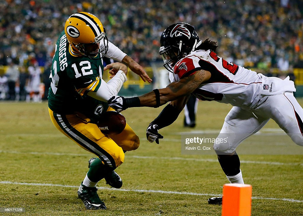 Aaron Rodgers #12 of the Green Bay Packers tries to maintain possession as Dwight Lowery #20 of the Atlanta Falcons defends in the first half at Lambeau Field on December 8, 2014 in Green Bay, Wisconsin.