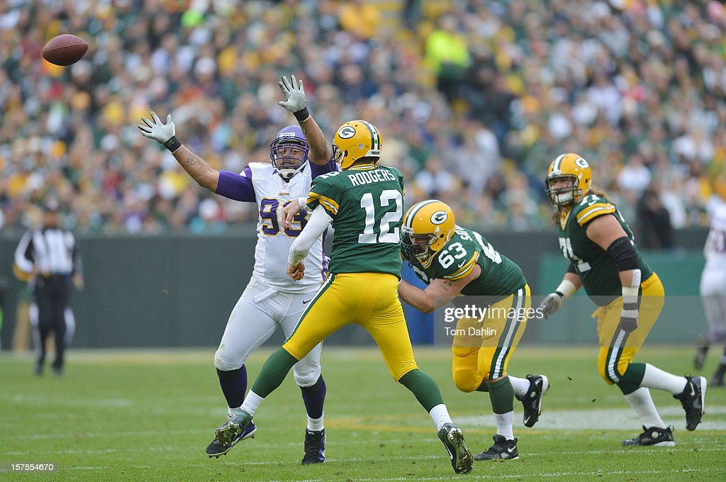 Aaron Rogers #12 of the Green Bay Packers passes the ball under pressure from Kevin Williams #93 of the Minnesota Vikings during an NFL game at Lambeau Field on December 2, 2012 in Green Bay, Wisconsin.