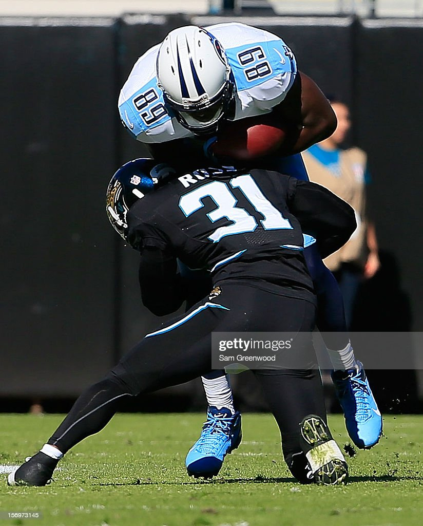 <a gi-track='captionPersonalityLinkClicked' href=/galleries/search?phrase=Aaron+Ross&family=editorial&specificpeople=2105852 ng-click='$event.stopPropagation()'>Aaron Ross</a> #31 of the Jacksonville Jaguars tackles Jared Cook #89 of the Tennessee Titans during the game at EverBank Field on November 25, 2012 in Jacksonville, Florida.