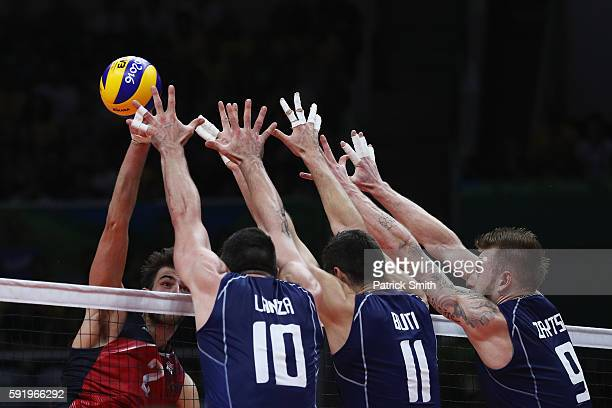 Aaron Russell of United States spikes against the Italy defence during the Men's Volleyball Semifinal match on Day 14 of the Rio 2016 Olympic Games...