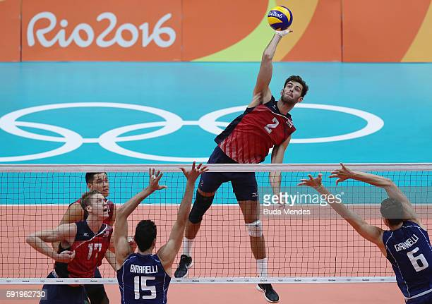 Aaron Russell of United States spikes at the Italy defence during the Men's Volleyball Semifinal match on Day 14 of the Rio 2016 Olympic Games at the...