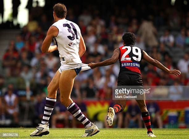Aaron Sandilands of the Dockers is tackled by the shorts from Alwyn Davey of the Bombers during the round two AFL match between the Essendon Bombers...