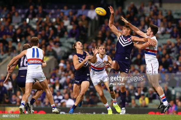 Aaron Sandilands of the Dockers taps the ball down to Nathan Fyfe during the round three AFL match between the Fremantle Dockers and the Western...