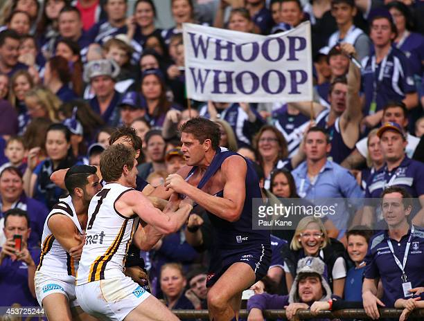 Aaron Sandilands of the Dockers wrestles with Paul Puopolo and Ben McEvoy of the Hawks during the round 21 AFL match between the Fremantle Dockers...