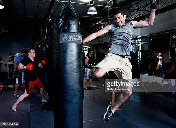Aaron Small jumps to kick the boxing bag during an exercise in the 'KM Bag' class taught by Kristine Ho at Krav Maga in Los Angeles