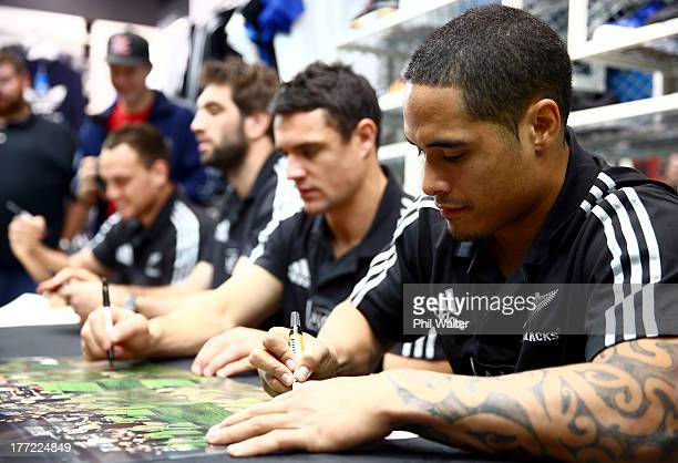 Aaron Smith of the All Blacks signs autographs during a New Zealand All Blacks adidas in store signing session on Lambton Quay on August 23 2013 in...