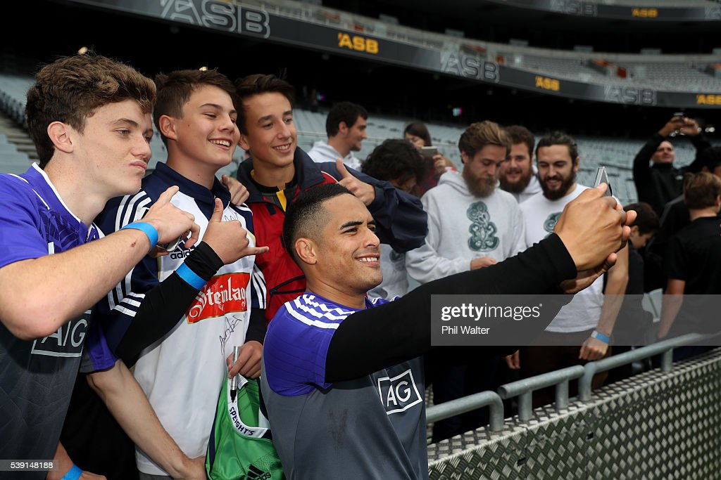Aaron Smith of the All Blacks takes a selfie with fans during a New Zealand All Blacks Captain's Run at Eden Park on June 10 2016 in Auckland New...