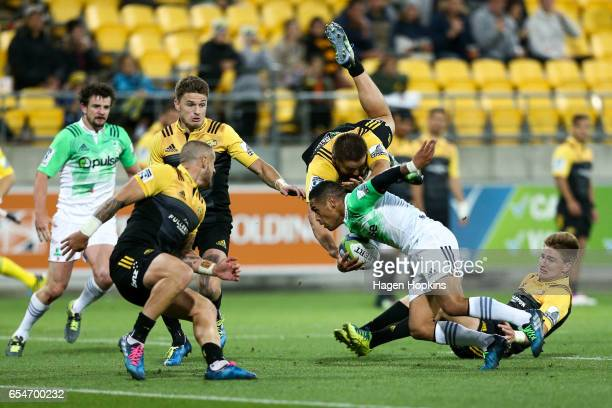 Aaron Smith of the Highlanders attepmts to break the defense of TJ Perenara Beauden Barrett Dane Coles and Jordie Barrett of the Hurricanes during...