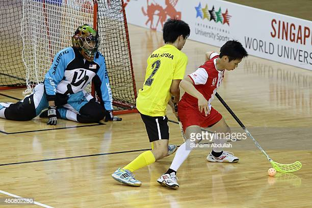 Aaron Tan En Jie of Singapore shields the ball from Chong Zephaniah of Malaysia during the World University Championship Floorball match between...