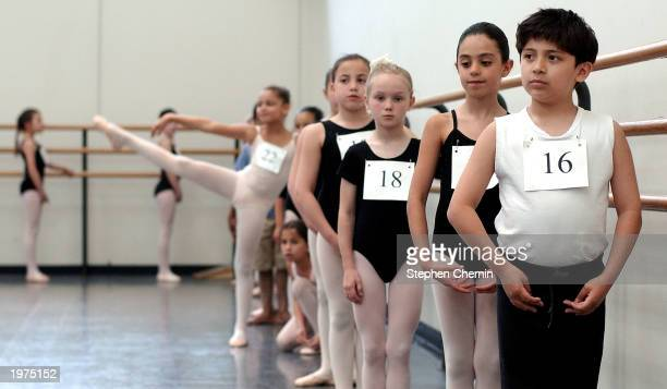Aaron Vivar strikes a ballet pose as he stands at the bar with other children during tryouts for spots in the School of American Ballet May 5 2003 at...