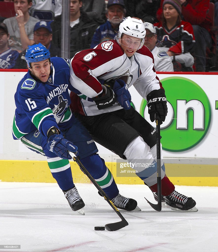 <a gi-track='captionPersonalityLinkClicked' href=/galleries/search?phrase=Aaron+Volpatti&family=editorial&specificpeople=7187520 ng-click='$event.stopPropagation()'>Aaron Volpatti</a> #15 of the Vancouver Canucks reaches for the puck while being held back by <a gi-track='captionPersonalityLinkClicked' href=/galleries/search?phrase=Erik+Johnson+-+IJshockeyer&family=editorial&specificpeople=457696 ng-click='$event.stopPropagation()'>Erik Johnson</a> #6 of the Colorado Avalanche during their NHL game at Rogers Arena January 30, 2013 in Vancouver, British Columbia, Canada. Vancouver won 3-0.