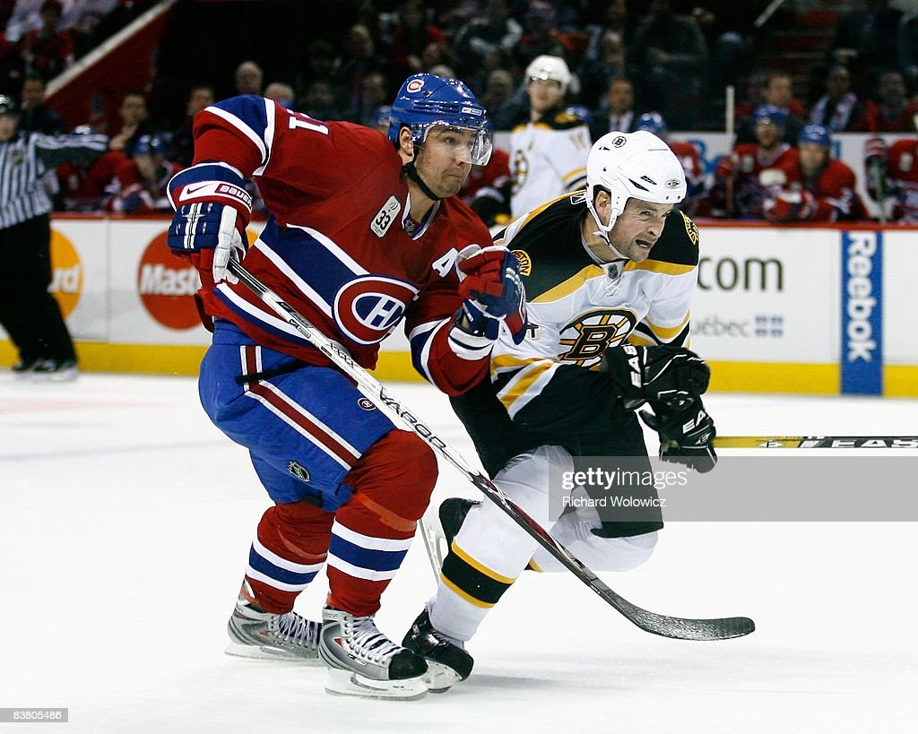 Aaron Ward of the Boston Bruins and Christopher Higgins of the Montreal Canadiens race to the puck during the game at the Bell Centre on November 22...