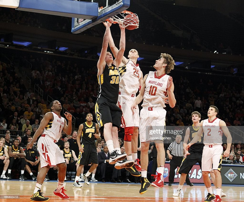 Aaron White #30 of the Iowa Hawkeyes dunks the ball past Alex Len #25 of the Maryland Terapins in the second half during the 2013 NIT Championship - Semifinals at the Madison Square Garden on April 2, 2013 in New York City.