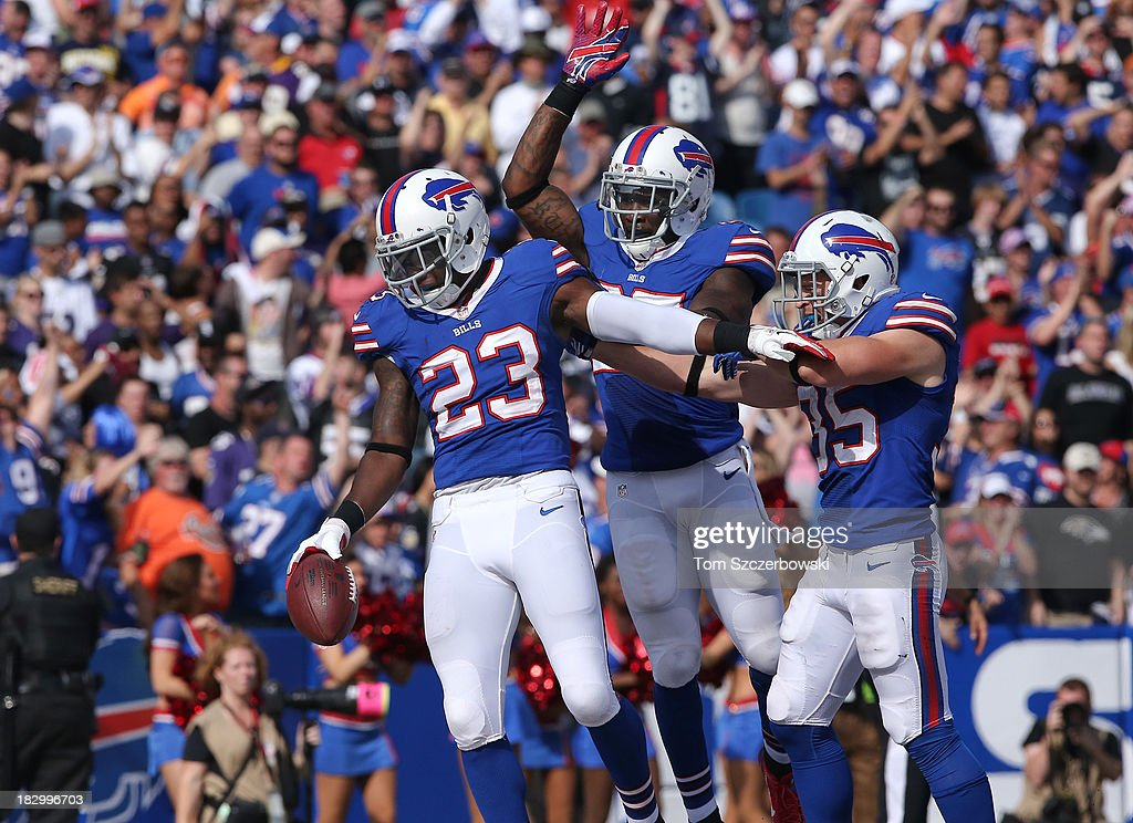 Aaron Williams #23 of the Buffalo Bills celebrates his interception with Da'Norris Searcy #25 and Jim Leonhard #35 during NFL game action against the Baltimore Orioles at Ralph Wilson Stadium on September 29, 2013 in Orchard Park, New York.