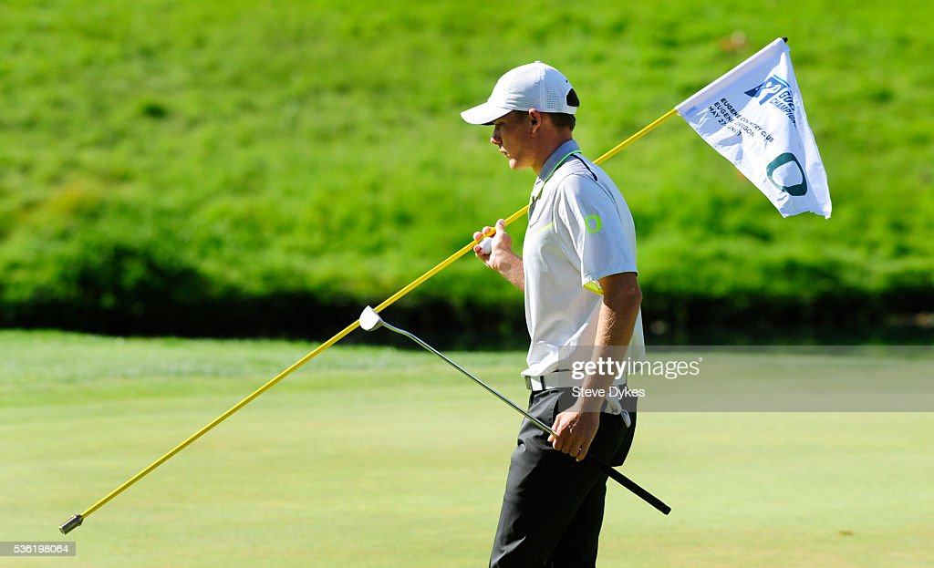 Aaron Wise of Oregon moves the flag stick on the 16th hole during round three of the 2016 NCAA Division I Men's Golf Championship at Eugene Country Club on May 31, 2016 in Eugene, Oregon.