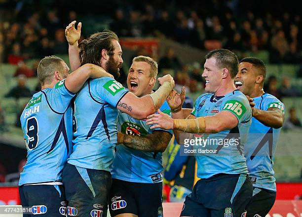 Aaron Woods of the Blues celebrates with Paul Gallen and his teammates after scoring a try during game two of the State of Origin series between the...