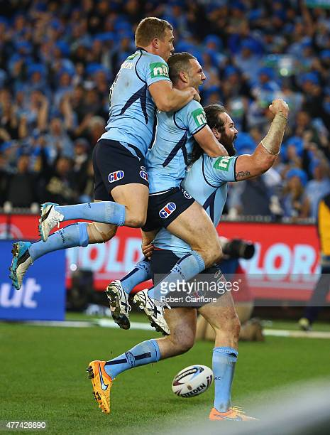 Aaron Woods of the Blues celebrates with Robbie Farah and Trent Hodkinson after scoring a try during game two of the State of Origin series between...