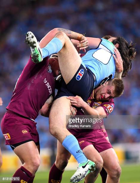Aaron Woods of the Blues is picked up by the defence during game three of the State Of Origin series between the Queensland Maroons and the New South...