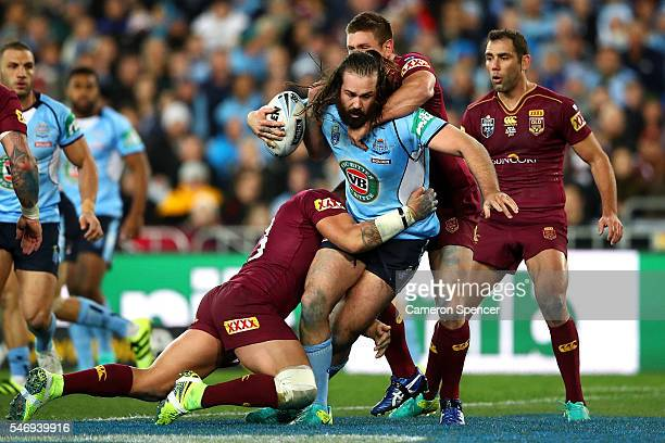 Aaron Woods of the Blues is tackled during game three of the State Of Origin series between the New South Wales Blues and the Queensland Maroons at...