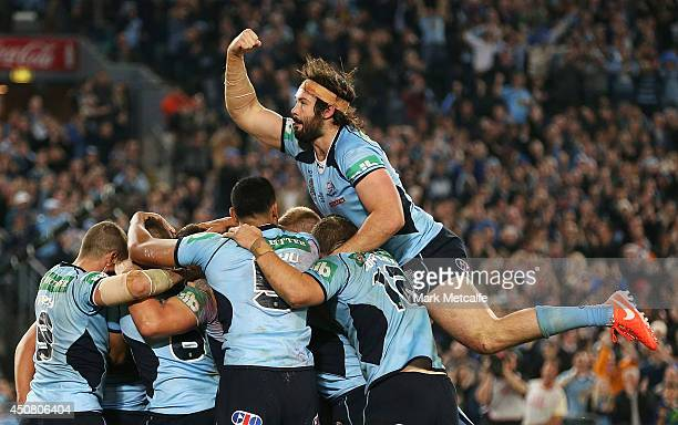 Aaron Woods of the Blues jumps onto his team mates to celebrate a try by Trent Hodkinson during game two of the State of Origin series between the...